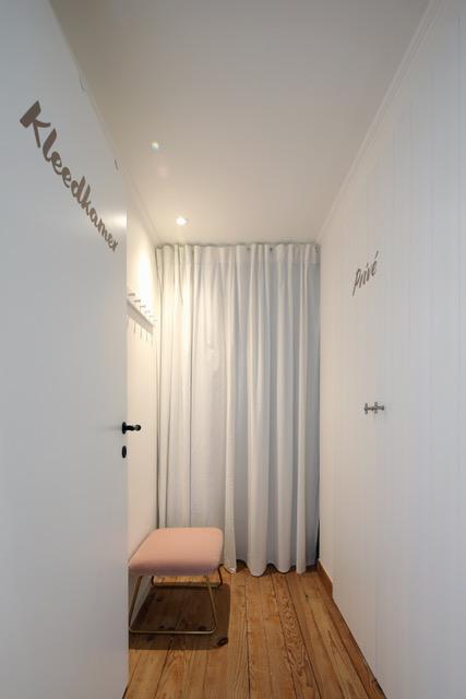 Kleedruimte sarasin clinic met gordijn voor kleedkamer en wachtbankje